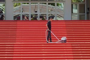 A man using vacuum cleaner to clean the stairs