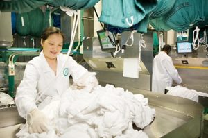 Alsco employee working on cleaning the linens